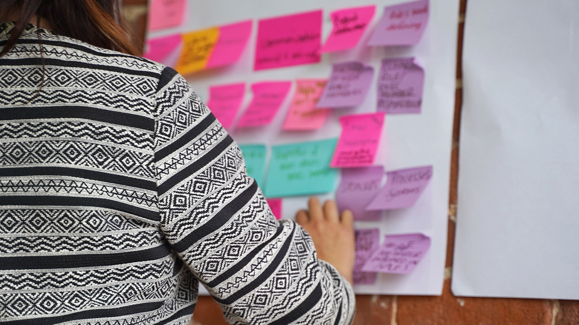 Lynda Henderson attaching sticky notes to the wall during a workshop
